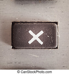 Symbol Multiplying - Old dirty and dusty rubberized button...