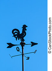 irony weather cock on a blue sky background