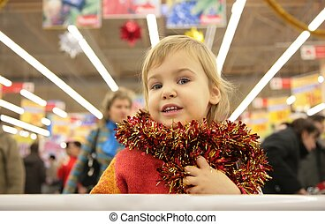girl with bright tinsel in store