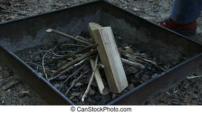 Woman adding wood on fire pit during camping in national...