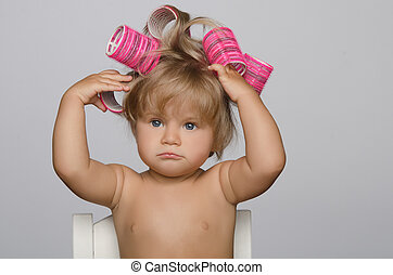 Little attractive kid with hair curlers on gray background