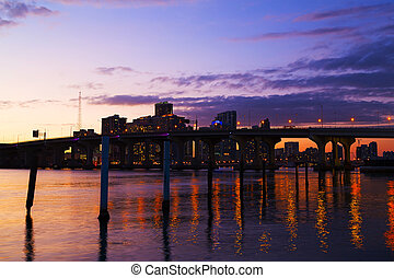 Miami city skyline with the bridge at sunset. Colorful buildings and bridge reflections of Miami downtown.