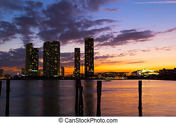 Dramatic sunset over Miami city downtown. Urban landscape and calm waters at sunset.