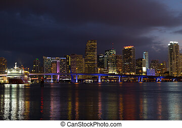 Night panorama of Miami city downtown with reflections. Colorful reflections of bridge, cruise ship and modern buildings.