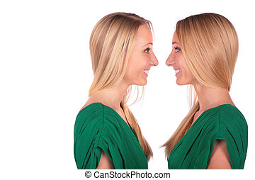Twin girls smiling face-to-face