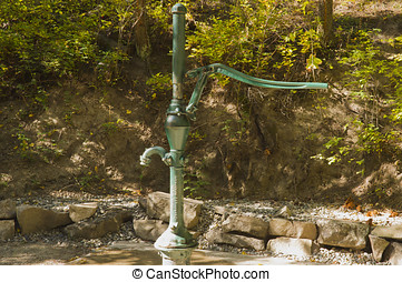 Water pump and well - An old hand pump sits atop a water...