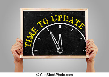 Time to update - Hands are holding the blackboard of time to...