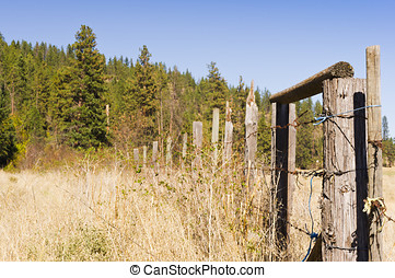 Wood and wire ranch fence - A wire and wood fence in a field...