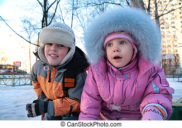 little boy and girl on street in winter 2