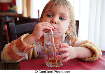 little girl drinks juice from glass through straw