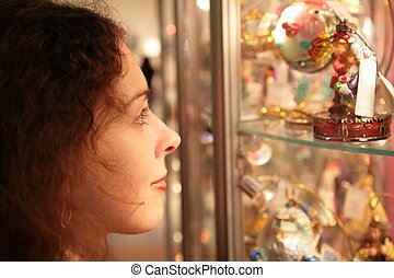 young woman looks on showcase with souvenirs