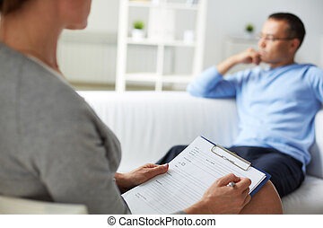 Man at psychologist - Woman psychologist filling in card of...