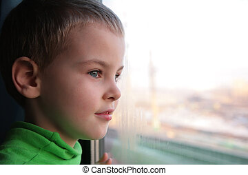 little boy looks in train`s window