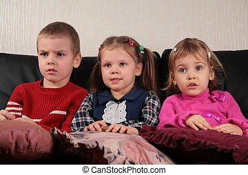 three children on sofa 2 watching tv