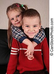 girl embraces boy for the neck on sofa