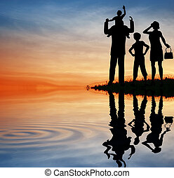 family silhouette on sunset sky water