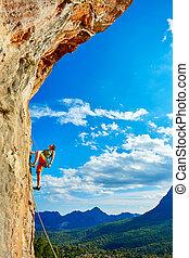 Rock climber climbing up a cliff - female rock climber...