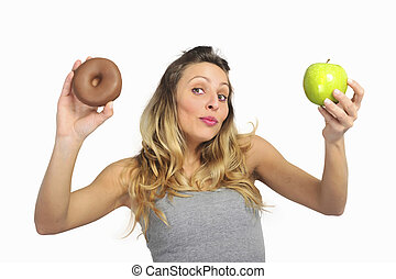 attractive woman holding apple and chocolate donut in...