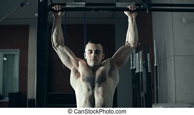 Body Conscious - Close up of bodybuilder pulling up in a gym