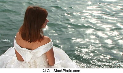Young Pretty Woman In White Dress Sitting On Rock By Sea -...