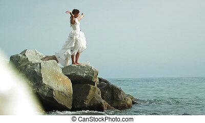 Young Woman In White Dress Standing On Rock By Sea -...