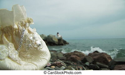 Young Woman In White Dress Sitting On Rock By Sea - Two...