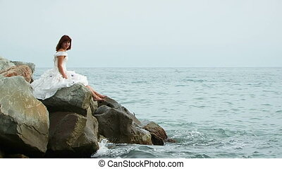 Beautiful Woman In White Dress Sitting On Rock By Sea -...