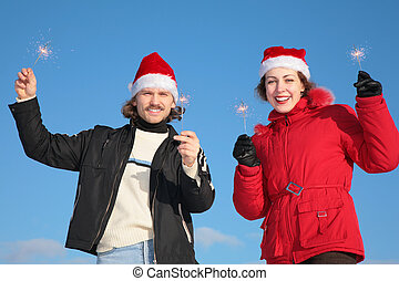 couple against blue sky background in winter in santa claus hats with sparklers