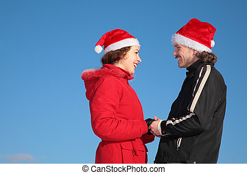 couple against blue sky background in winter in santa claus hats stand face to face