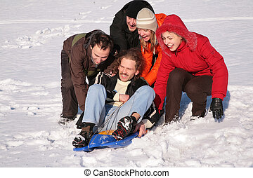 group of friends push another one on plastic sled