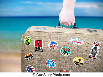 hand holds a suitcase with stickers on background of ocean