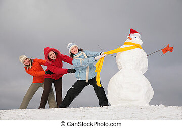 Three young girls pull snowman by yellow scarf