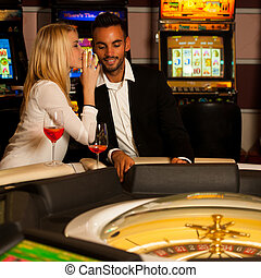 Young couple playing roulette in casino betting and winning...