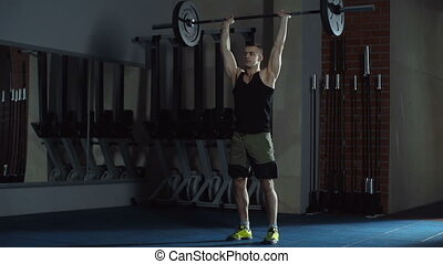 Overhead Squats - Close up of athletic man performing...
