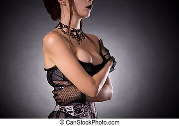 Busty woman in Victorian corset embracing herself - Busty...