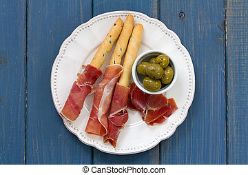 prosciutto with olives on white plate