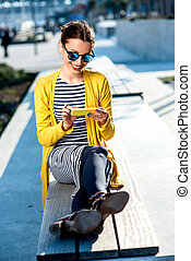 Woman with phone outdoors - Young woman in yellow sweater...
