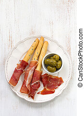 prosciutto with olives on plate