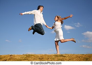 man jumps on meadow hold girl from hand