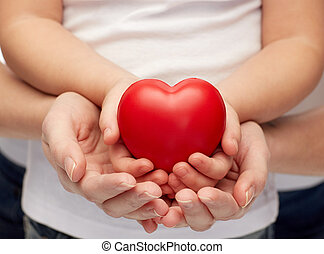 close up of woman and girl hands holding heart - people,...
