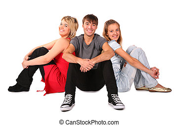 Boy and two girls sits on floor