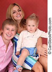 smiling young family in red room