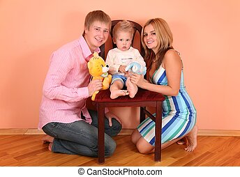 parents with son on chair in pink room