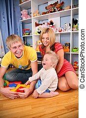 mother and father with child in playroom