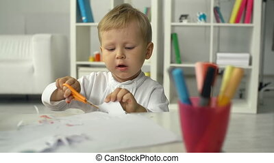 Childhood Hobby - Close up of boy busy cutting paper figures