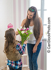 Mothers Day - Girl gives her mom a big bouquet of tulips,...