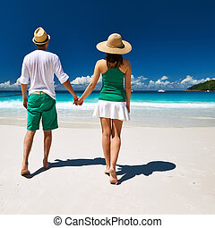 Couple in green walking on a beach at Seychelles - Couple in...