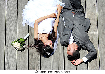 romantic newlywed couple lying down together in sunny day -...