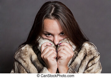 girl hiding in fur coat - beauty girl with brown hair hiding...
