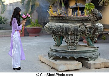 Young Asian woman making a votive offering of fresh pink...